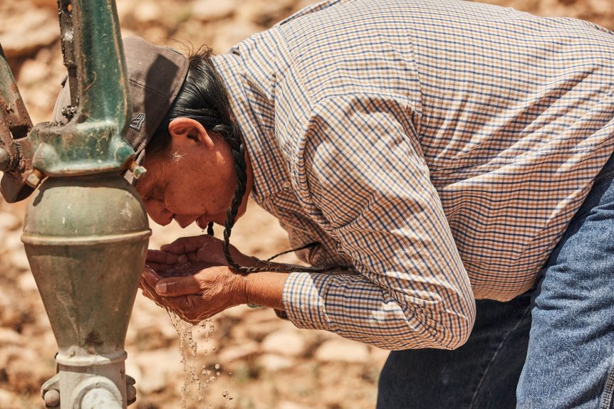 Man drinks from water pump
