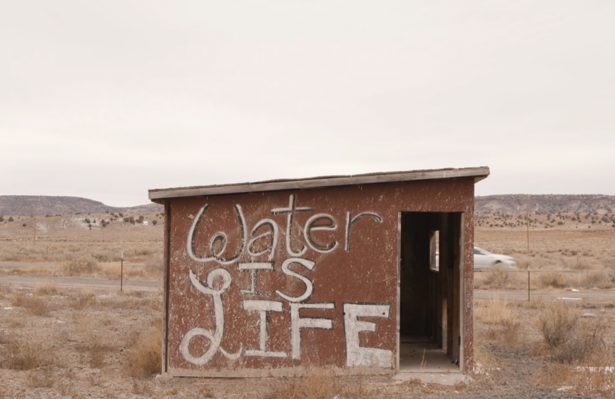 "shed with ""Water is Life"" painted on side"