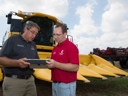 Precision agriculture experts talking, farm machinery